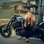 a sexy lady sitting next to a custom Dnepr motorcycle