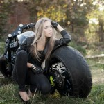 a hot chick sitting next to a custom bike