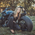 an attractive lady and a custom motorcycle
