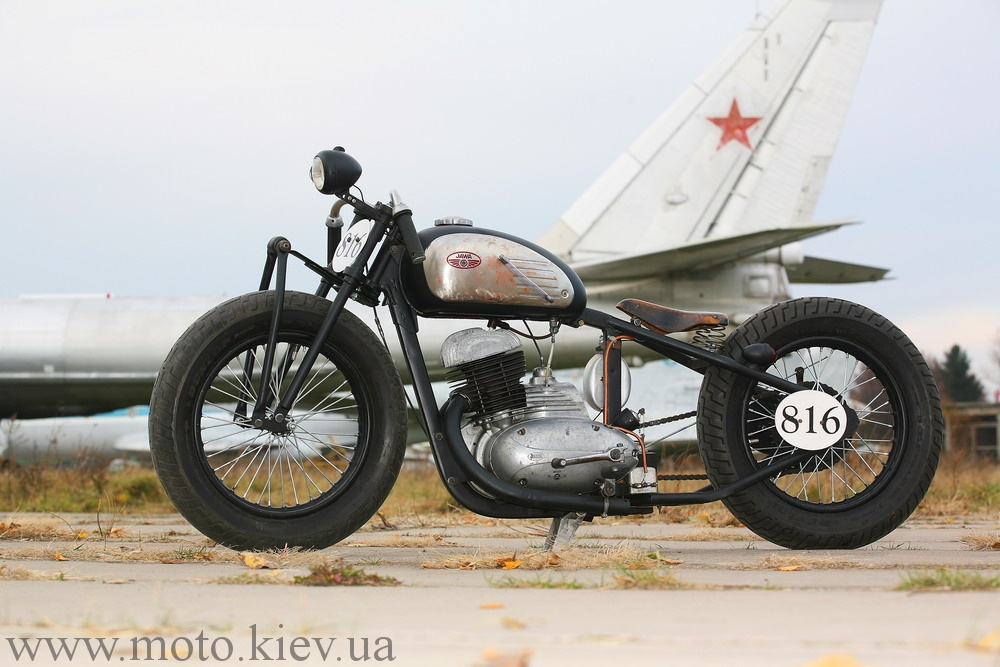 a custom Jawa bobber near an airplane