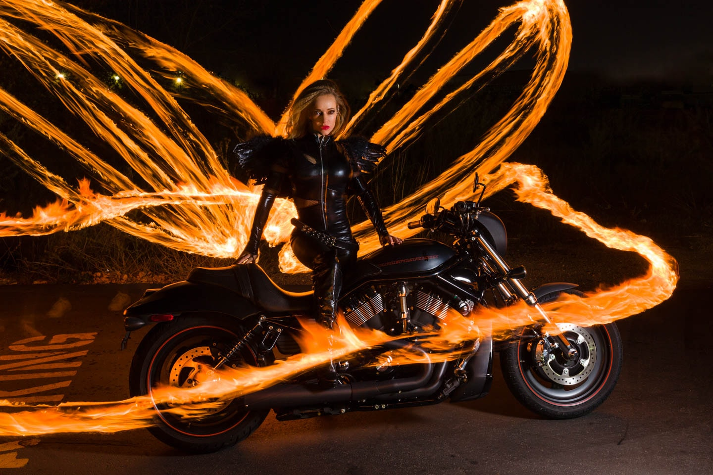 a hot girl on a motorcycle surrounded by flame