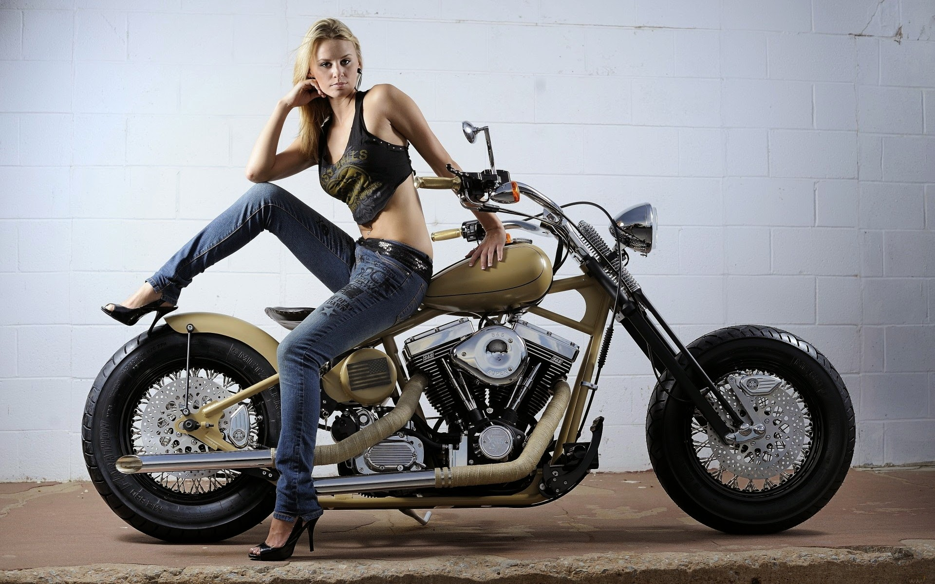 an attractive blond girl sitting on a harley motorbike